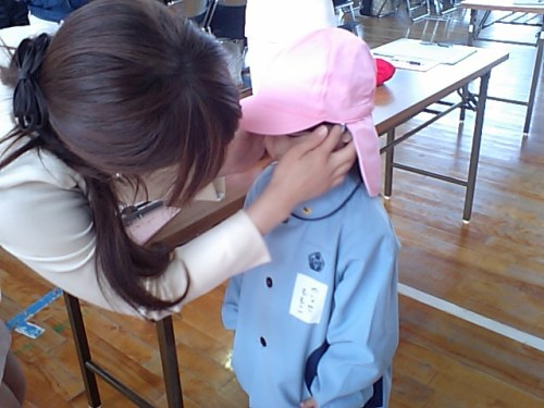 She met with her teacher at first time and was put on the pink cap by the teacher.